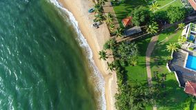 Aerial of sea waves and sandy beach near the hotel that washing by sea waves in Sri Lanka. Light waves washing sandy beach with palm trees and boats near the stock video footage