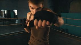Light weight boxer punch the camera on the ring in vintage gym. Lightweight boxer punch the camera on the ring in stylized vintage gym. Caucasian man training stock footage