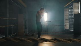 Light weight boxer training on the ring in vintage stylized gym. Lightweight boxer training hard in stylized gym. Caucasian young man fight the shadow on the old stock video footage