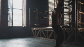 Light weight boxer training in vintage stylized gym near the ring. Lightweight boxer training in stylized gym. Caucasian young man fight the shadow near the old stock video footage