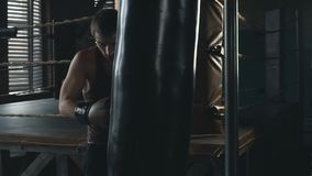 Light weight boxer training in vintage stylized gym slowmo. Lightweight boxer training in dark vintage stylized gym. Caucasian young man with boxing gloves stock footage