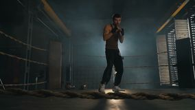 Light-weight caucasian man boxing on the ring in light rays. Kickboxer training in industrial gym interior. Slow motion stock video