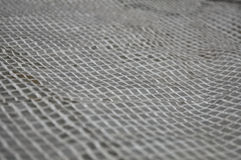 Light wicker grille on a gray background. Royalty Free Stock Image