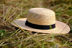 Light wicker hat on hay. High quality photo of a classic broad-brimmed hat: you may see classic wicker hat with dark navy blue almost black fabric strip around royalty free stock photography