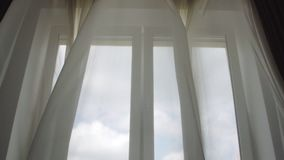 Light wind blows through open window and waves curtains. Light wind blows through open window and waves white transparent curtains against cloudy sky outside stock video footage