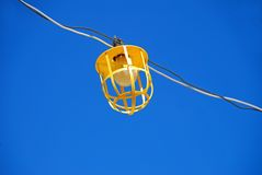 Light on Wire. Construction utility light and bulb on wire across blue sky Stock Photography