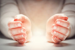 Light between woman's hands in gesture of protection, care. stock photos