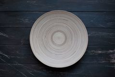 Light wood plate on dark wood backdrop royalty free stock photography
