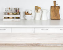 Light wood table with bokeh image of kitchen counter interior