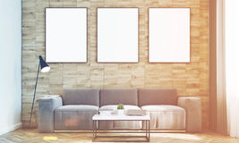 Light wood walls living room, front, toned. Front view of a living room with light wooden walls, a long sofa and three framed vertical posters hanging above it Royalty Free Stock Images