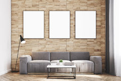 Light wood walls living room, front. Front view of a living room with light wooden walls, a long sofa and three framed vertical posters hanging above it. 3d Royalty Free Stock Photography