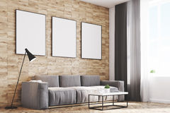 Light wood walls living room, side. Side view of a living room with light wooden walls, a long sofa and three framed vertical posters hanging above it. 3d Royalty Free Stock Images