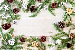 On a light wooden background in a circle frame made of fir branches, gold and silver ribbons and cones. Copy space. Festive layout with place for text stock images