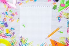 Light wooden background with colored pencils on the sides of the clipped notebook, there is a place for writing in the middle. stock image