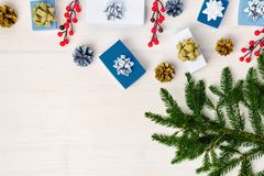 On a light wooden background are fir branches. Near the red berries, small boxes and cones. Gifts decorated with silver stock photos