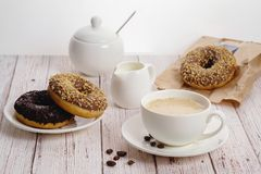 Morning breakfast with chocolate donuts and cup of coffee with cream on light wooden background.Delicious donuts sprinkled with cr stock images