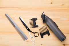 Light wooden background, are objects for cutting hair and beard and styling, electric machine. stock image