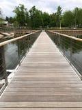 Light wooden bridge on the water with iron handrails. Light wooden bridge on the water royalty free stock photos