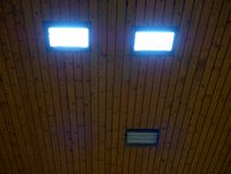 Light from wooden ceiling of sporting building, energy saver light panels Stock Photos