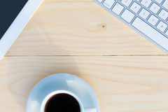 Light Wooden Desk Top View with Business and Every Day Life Items Electronics and Coffee Mug Royalty Free Stock Photography