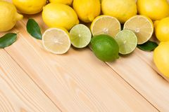On a light wooden table, sliced lemons and lime royalty free stock image