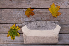 Light wool sweater with a maple leaf on old background. Royalty Free Stock Images