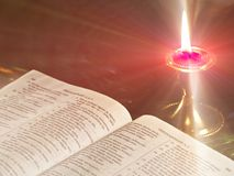 Light in the world. Open Bible in candlelight Royalty Free Stock Photos