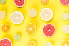 On a light yellow background, lie a sliced grapefruit with other fruits royalty free stock photos