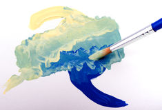 Light yellow and dark blue paint mixed into green Stock Image