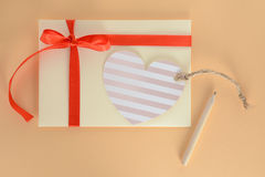 Light yellow envelope with a red ribbon, heart card and pencil on an apricot background Stock Photos