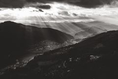 Lightbeams enlighten the valley. Lightbeams enlighten a valley in the French Alps on a cloudy day Vestiges du Chateau de Rochebonne, Saint-Jean-Roure, France stock photography
