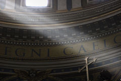 Lightbeams falling on a cross. Lightbeams falling through the windows of the dome of Saint Peter's Basilica on the cross of the altar, Vatican, Rome, Italy Royalty Free Stock Images