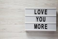 """Lightbox με το κείμενο """"αγάπη εσείς περισσότεροι """"σε μια άσπρη ξύλινη επιφάνεια Βαλεντίνος ` s ημέρα στις 14 Φεβρουαρίου διάστημα στοκ εικόνα"""