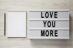 "Lightbox με το κείμενο ""αγάπη εσείς περισσότεροι "", κενά σημειωματάριο και μολύβι σε ένα άσπρο ξύλινο υπόβαθρο Βαλεντίνος ` s ημέ στοκ φωτογραφίες με δικαίωμα ελεύθερης χρήσης"