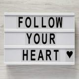 """Lightbox con testo """"segue il vostro cuore """"su un fondo di legno bianco, vista superiore Disposizione piana, sopraelevata Bigliett fotografia stock"""