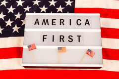 America First. Lightbox with letters - AMERICA FIRST - on an american national flag Stock Photography