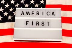 America First Slogan. Lightbox with letters - AMERICA FIRST - on an american national flag Royalty Free Stock Photo