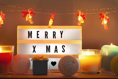 Merry X-mas lightbox and Christmas decorations with gift royalty free stock images