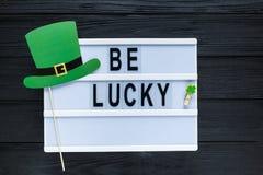 Lightbox met titel is gelukkige en photobooth groene hoed op houten stokken bij groene achtergrond Creatieve achtergrond van St P stock afbeelding