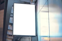 Lightbox mounted on the wall of a building in the business district at night.  Stock Photo