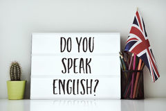 Question do you speak English?. A lightbox with the question do you speak English? written in it, a cactus, a pot of pencils and a flag of the United Kingdom on Royalty Free Stock Image