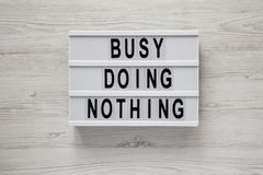 Lightbox with text `Busy doing nothing` on a white wooden background, top view. From above, flat lay, overhead royalty free stock photography