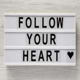 Lightbox with text `Follow your heart` on a white wooden background, top view. Flat lay, overhead. Valentine`s Day 14 February stock photography