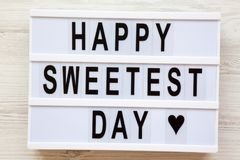 Lightbox with text `Happy Sweetest Day` word over white wooden background, top view. From above, flat lay, overhead.  royalty free stock images