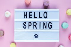 Lightbox with title Hello spring and macaroons on pink background. Decoration, spring background. Top view stock photography