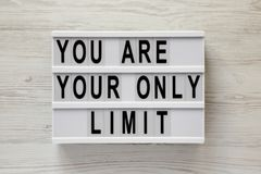 Lightbox with `You are your only limit` words over white wooden background, top view. Overhead, from above. Flat lay.  stock photos