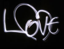 Lightbrushed Heart Against Black. Heart and letters painted with light on long time exposure of camera (bulb mode). This kind of photography is called lightbrush Stock Photo