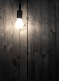 Lightbulb. Glowing lightbulb in front of wooden wall with copyspace - inspiration or idea concept Stock Images