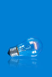 Lightbulb on blue background with reflection Stock Image