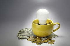 Lightbulb and Cup full with money - Finance Concept Royalty Free Stock Images